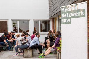 Teilnehmer:innen vom Gametreff NRW in Köln sitzen vor der School of Games und vernetzen sich. Im Vordergrund ein Mediennetzwerk.NRW-Banner.