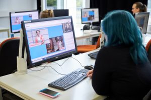 Skilltree.NRW - Coaching für die Games Branche. Teilnehmerin verfolgt Workshop auf Monitor.